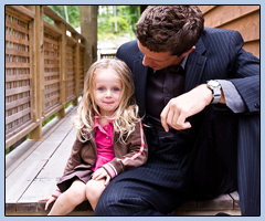 Man in a suit holding a little girl