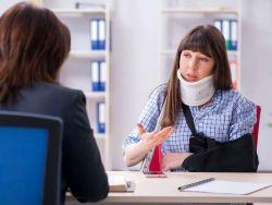 Woman in a neck brace sitting across from a lawyer