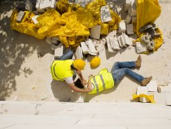 Construction worker hurt on the ground being helped by another worker