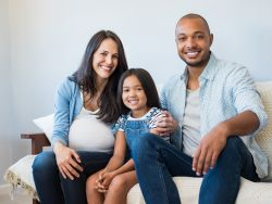 Pregnant mother, father, and daughter sitting on a couch