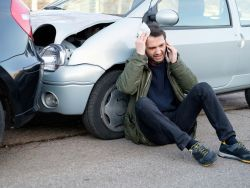 Man resting against his crashed car while making a phone call