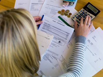 Woman paying bills and using a calculator