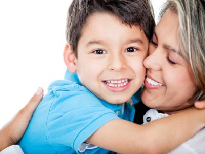 Smiling woman hugging young smiling boy