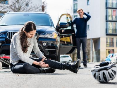Sitting woman holding her knee next to a bike and helmet and a man with his arm on his head standing on the driver's side of a car