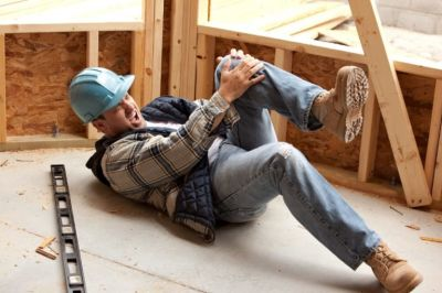 Construction worker holding knee in pain