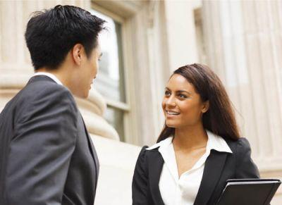 Women in suit holding padfolio speaking to man in suit