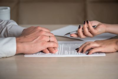 Close up of a man and woman's hand over a document