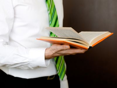Man in suit reading book