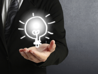 Man in suit with hand out and graphic/drawing of a lightbulb above his hand