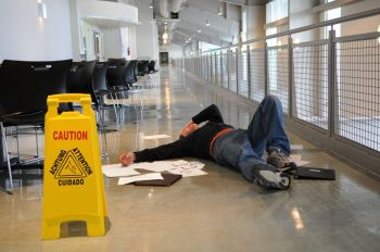 Man on the floor with his hand on his face near a wet floor sign