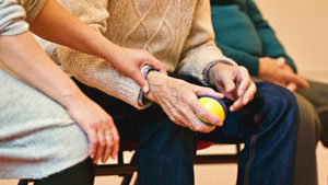 Elderly person sitting down while holding a ball