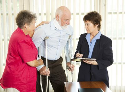Elderly woman standing next to elderly man on crutches and wearing a neck brace speaking to a woman in a suit holding a clipboard