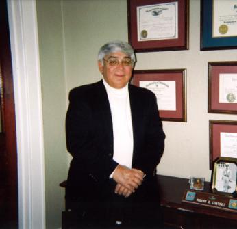 Bob Sr. Standing in front of framed awards