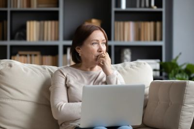 Older woman sitting with computer on her lap and hand to her face looking away