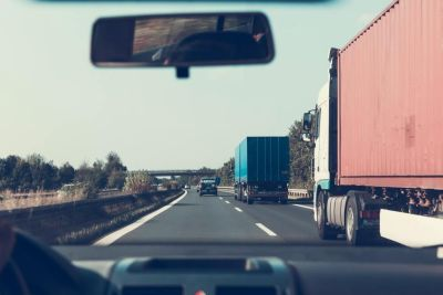 View from inside a car on a road with two semi trucks on the right