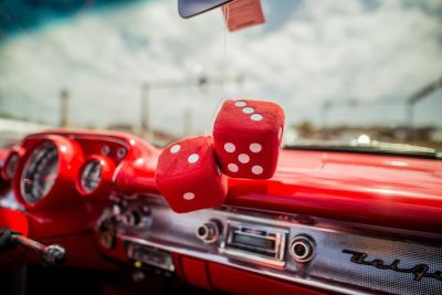 Two red dice decor hanging inside car with red interior