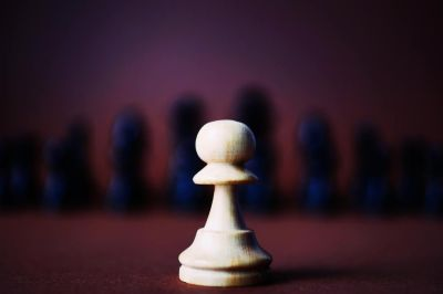 One white pawn with black chess pieces in the background